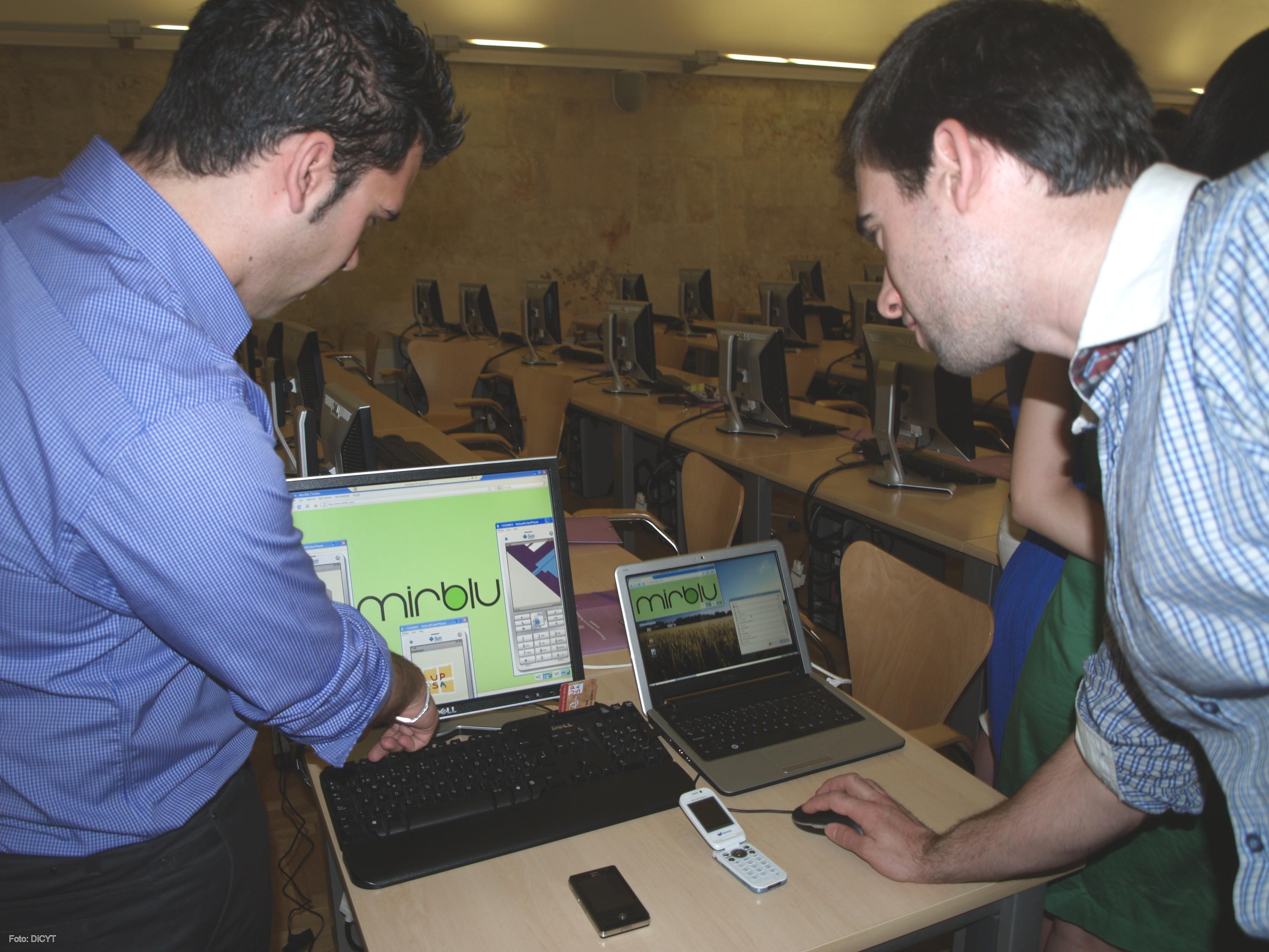 Los dos jóvenes emprendedores muestran su trabajo en el ordenador.
